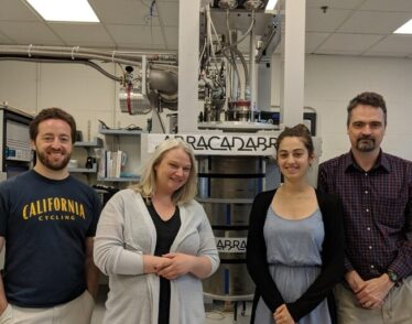 Four team members standing in front of ABRACADABRA, the instrument used to detect axions.