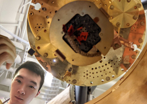 Zhiren (Isaac) Zheng holds up a sample of the new ferroelectric structure created by MIT researchers and colleagues