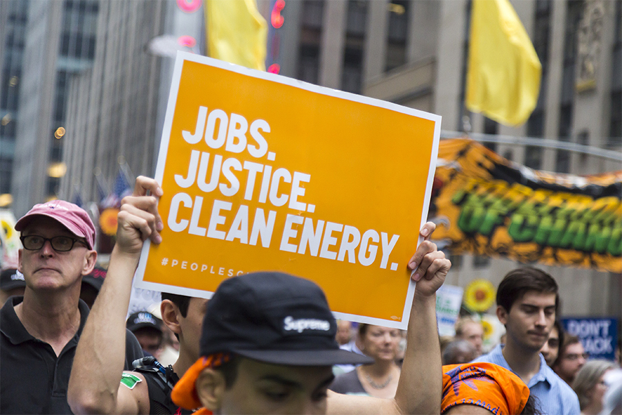 """Photo from the March for Science showing a sign reading """"Jobs, Justice, Clean Energy. #peoplesclimate"""""""