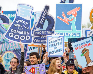 Photo from the March for Science in Washington D.C. showing smiling people holding pro-science signs.