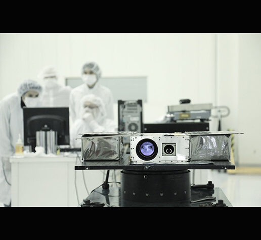 Members of the ASTERIA team prepare the petite satellite for its journey to space.