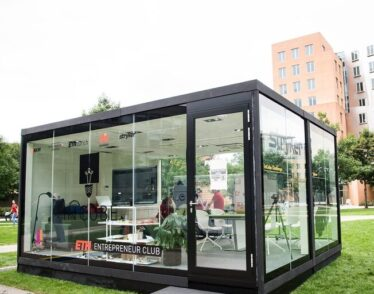 Photo of a glass cube on MIT's North Court that five students were challenged to live and work in.