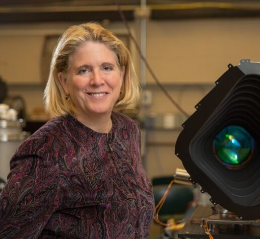 Jacqueline Hewitt stands with a prototype of one of the four cameras aboard the Transiting Exoplanet Satellite Survey (TESS) instrument.