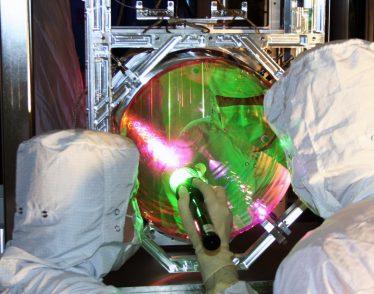 LIGO optics technicians examining one of LIGO's mirrors.