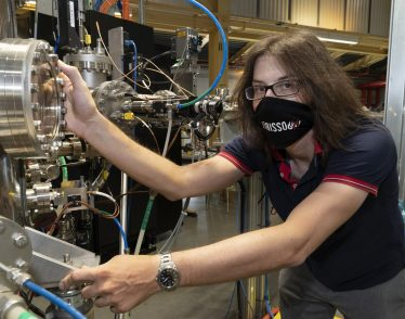 Photo of Jonathan Pelliciari in a lab, wearing a face mask and holding onto a large instrument with many metal knobs and wires.