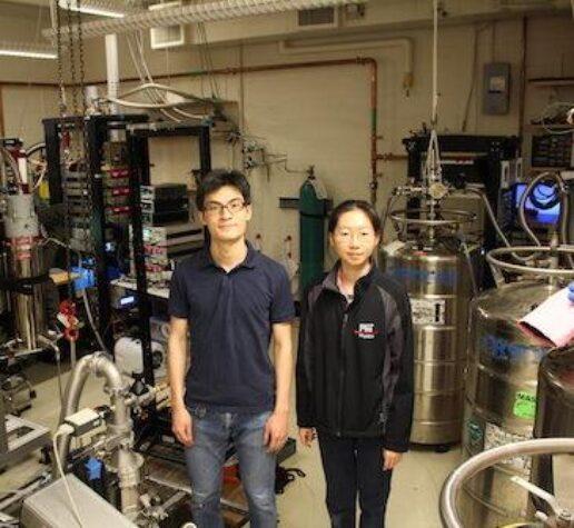 Physics postdoc and grad student stand in MIT lab.