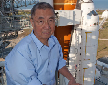 Professor Ting poses in front of the Space Shuttle Endeavor before it launches with AMS-02